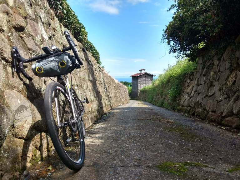 view of Spartacus bike in a small walled uphill road