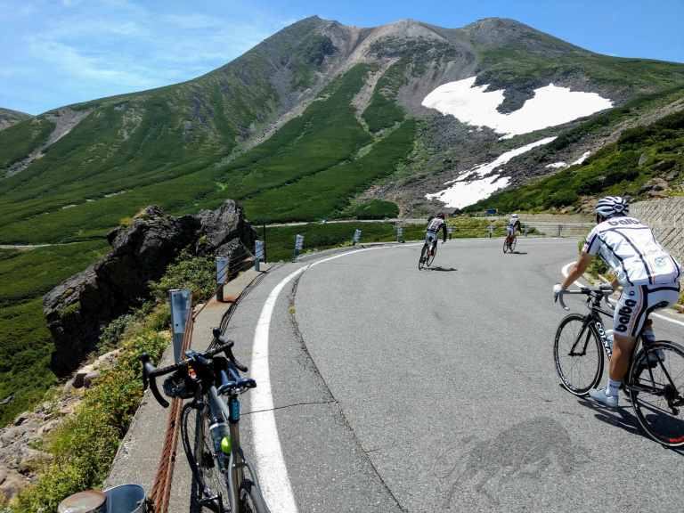Photo of cyclist going down the summer sunny mountain road