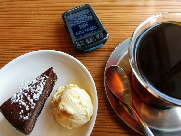 a cup of coffee, chocolate cake and vanilla beside on a wood table